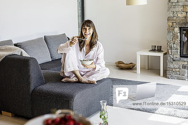Portrait of smiling woman having breakfast on couch at home