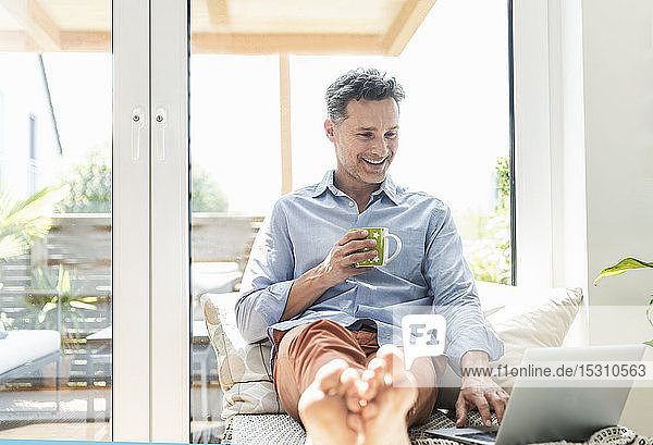 Mature man sitting on couch  using laptop  drinking coffee