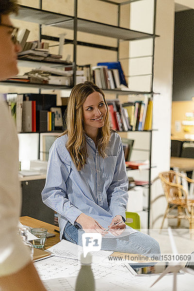Smiling businesswoman looking at colleague in office