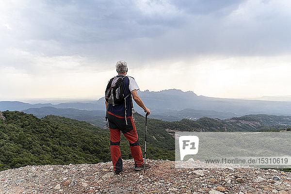 Senior-Wanderer mit Wanderstock auf Aussichtspunkt stehend