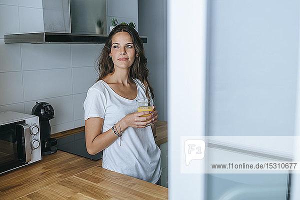 Junge Frau steht in der Küche mit einem Glas Orangensaft