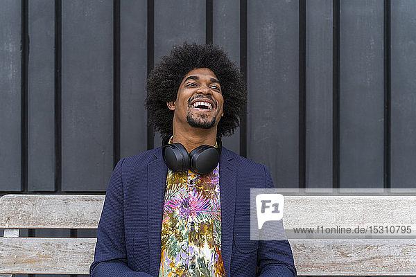 Lachender stilvoller Mann sitzt auf einer Bank