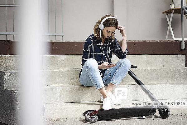 Junge Frau mit Elektroroller  die auf einer Treppe sitzt und Musik hört