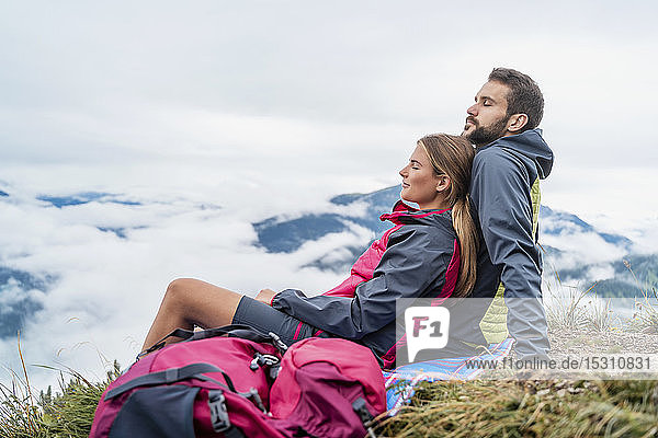 Affectionate young couple on a hiking trip in the mountains having a break  Herzogstand  Bavaria  Germany