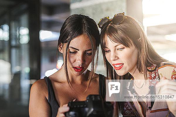 Zwei junge Frauen überprüfen Fotos auf einer Kamera