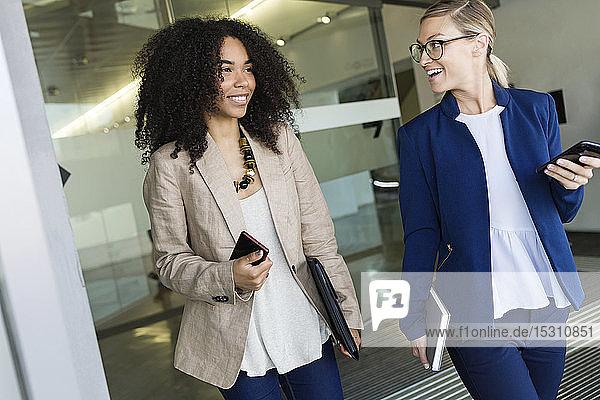 Zwei fröhliche junge Geschäftsfrauen gehen und reden in einem Flur