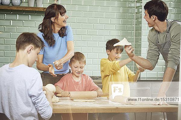 Mutter und Söhne bereiten zu Hause Pizza zu