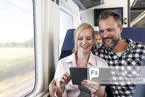 Ehepaar mit digitalem Tablett in einem Zug