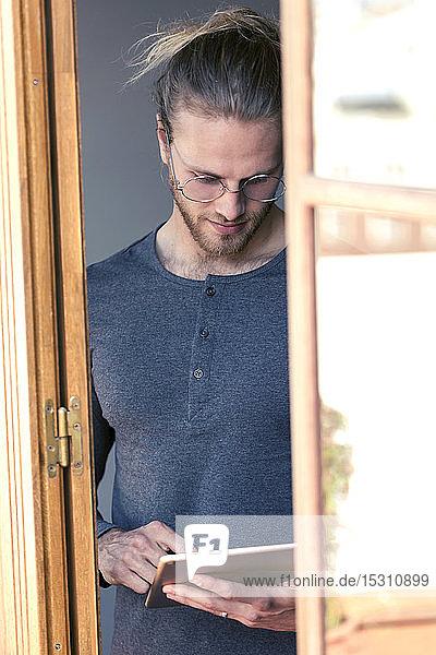 Junger Mann benutzt zu Hause ein digitales Tablett