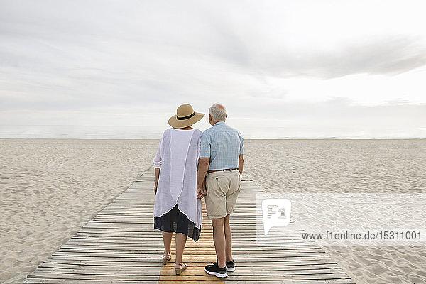 Rückenansicht eines älteren Ehepaares  das Hand in Hand auf einer Holzbalkenpromenade steht und auf den Horizont schaut  Liepaja  Lettland