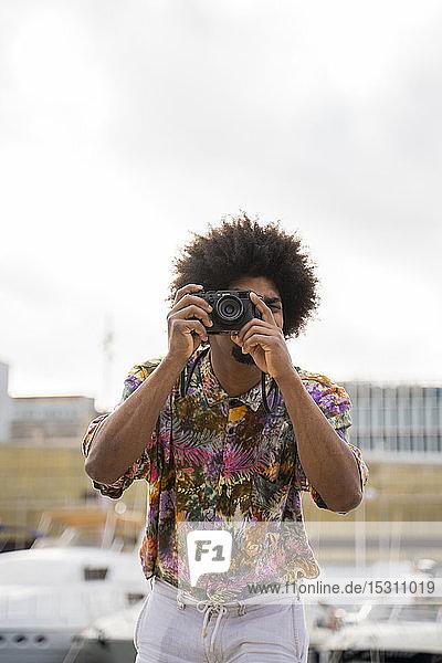 Mann mit farbigem Hemd fotografiert mit einer Kamera