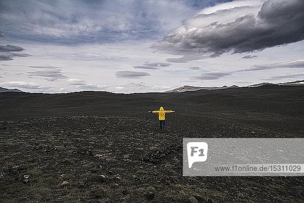 Erwachsener Mann steht mit ausgestreckten Armen im isländischen Hochland