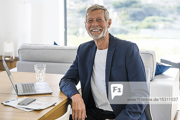 Portrait of smiling senior businessman with laptop sitting at desk at home
