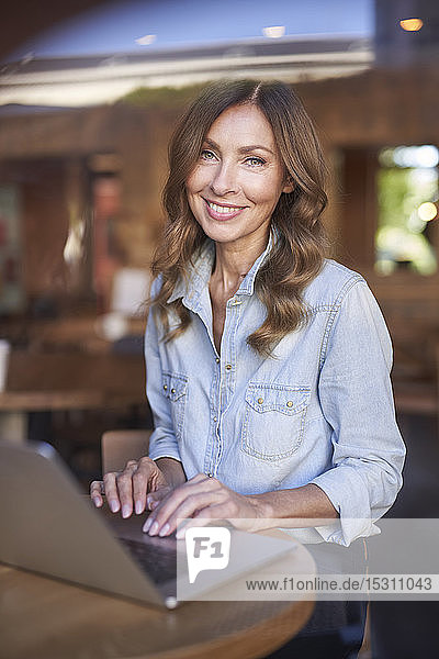 Business woman using laptop in a cafe