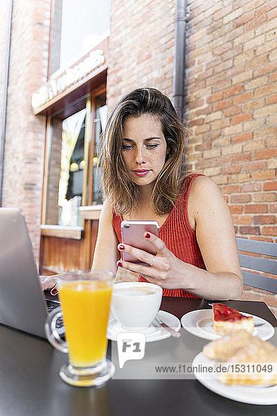 Porträt eines jungen Bloggers  der im Straßencafé sitzt und auf sein Handy schaut