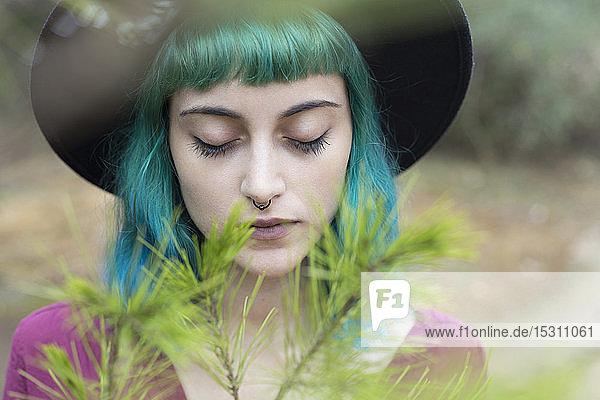Bildnis einer jungen Frau mit gefärbten blauen und grünen Haaren und Nasenpiercing in Natur
