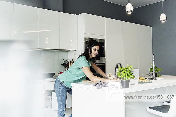 Frau benutzt Laptop in der Küche