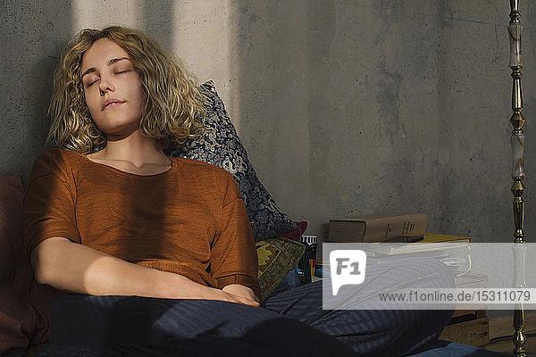 Porträt eines Studenten  der entspannt auf dem Bett sitzt