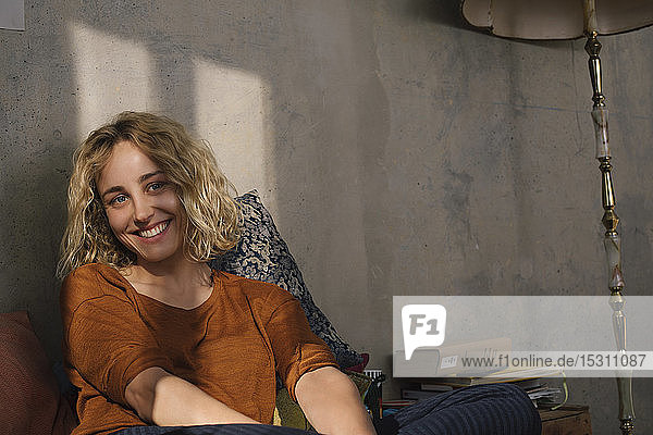 Porträt eines lächelnden Studenten  der zu Hause auf dem Bett sitzt