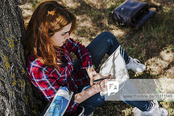 Redheaded motorcyclist leaning against tree trunk taking notes