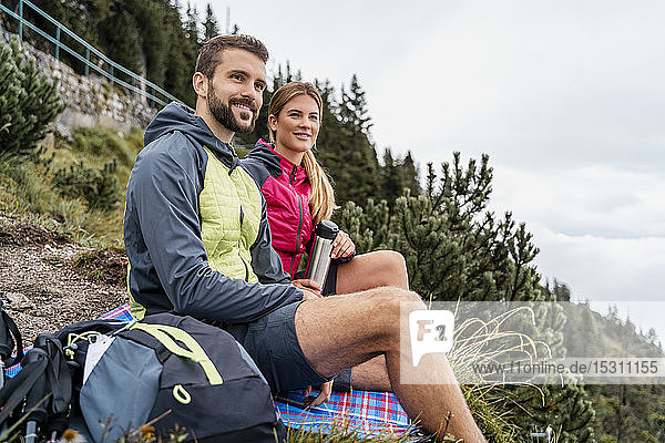 Young couple on a hiking trip in the mountains having a break  Herzogstand  Bavaria  Germany