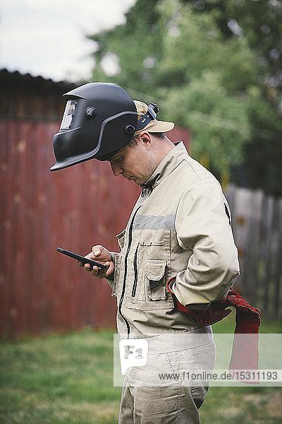Mann mit Schweißgerät  im Hinterhof stehend  mit Smartphone