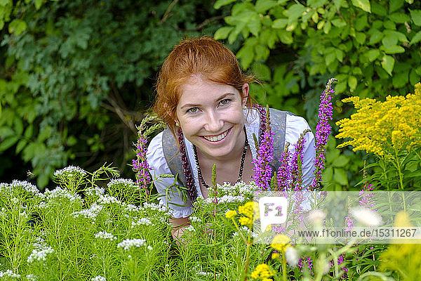Porträt einer rothaarigen Teenagerin im Garten