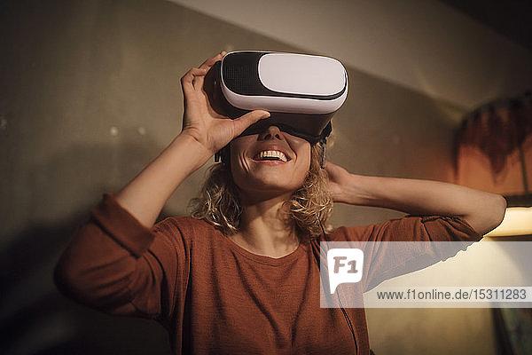Lachende junge Frau setzt zu Hause eine Virtual-Reality-Brille auf