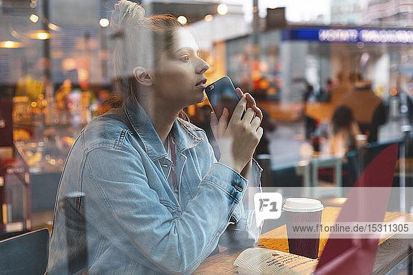 Junge Frau mit Smartphone in einem Cafe