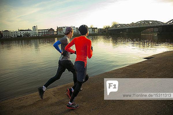 Zwei junge Männer joggen entlang der Themse  London  UK
