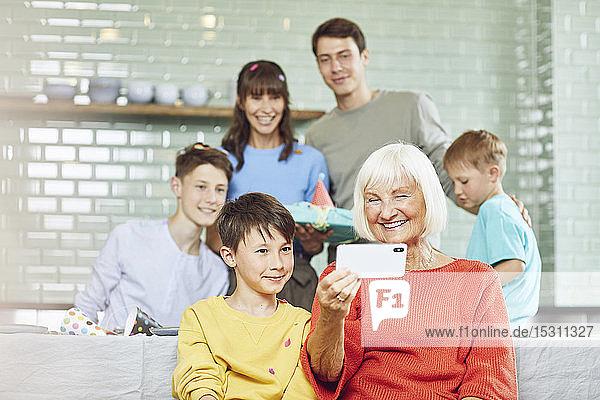 Mutter und Söhne feiern Großmutters Geburtstag in ihrer Küche  Junge nimmt sich selbst