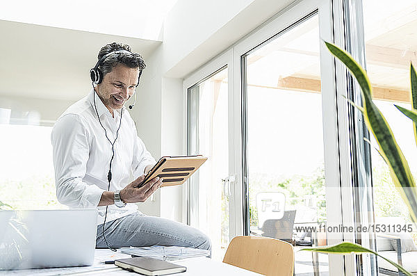 Businessman in bright office having conference call  using headset and digital tablet