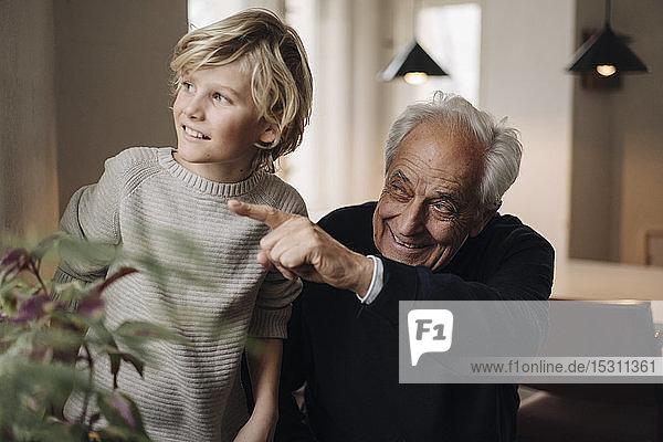 Großvater und Enkel zu Hause  die aus dem Fenster schauen