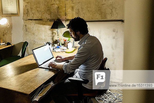 Businessman using laptop on table in the dark