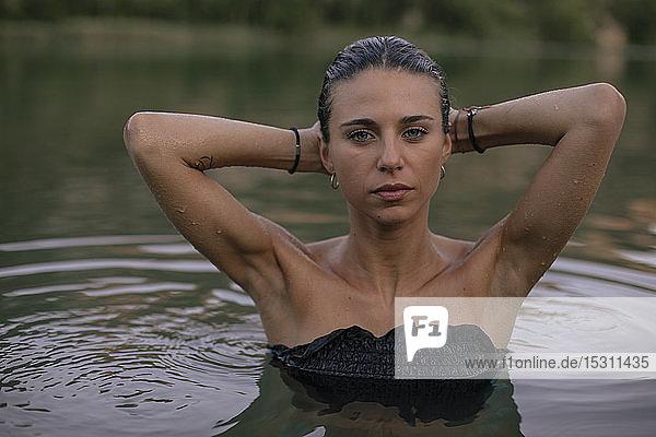 Porträt einer jungen blonden Frau  die in einem See badet