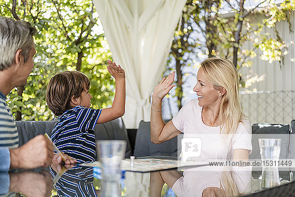 Happy mother and son high fiving after winning a game on terrace