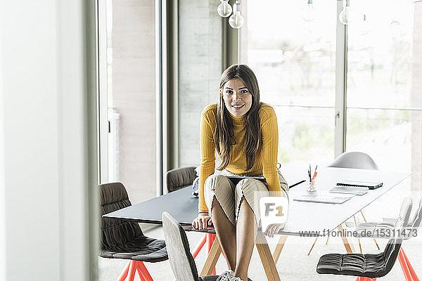 Porträt einer selbstbewussten jungen Geschäftsfrau  die im Büro auf dem Tisch sitzt