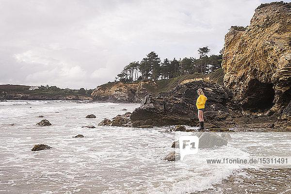 Frau in gelber Regenjacke steht auf Felsen am Strand