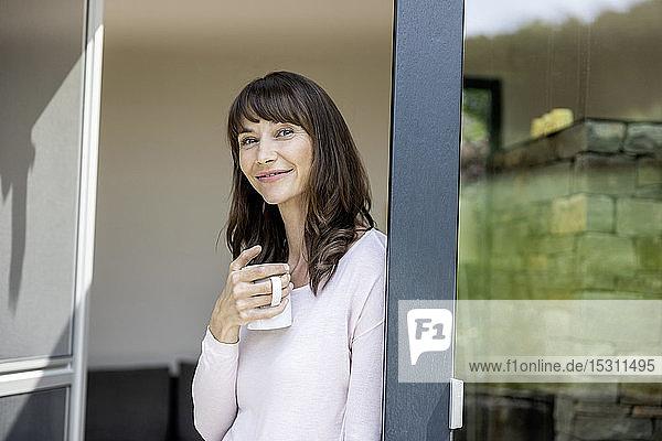 Porträt einer lächelnden Frau  die zu Hause eine Tasse Kaffee hält
