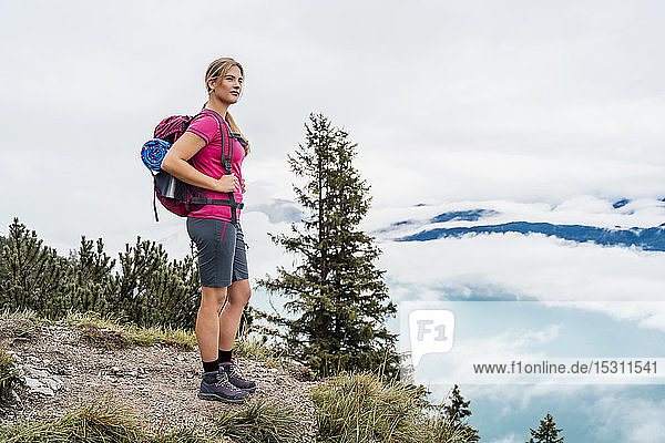 Young woman on a hiking trip in the mountains looking at view  Herzogstand  Bavaria  Germany