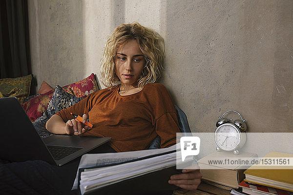 Porträt einer blonden Studentin im Bett bei der Arbeit am Laptop
