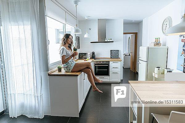 Junge Frau sitzt mit einem Getränk auf der Küchentheke