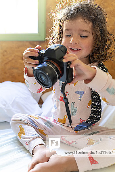 Cute little girl in pajamas in bed with a camera