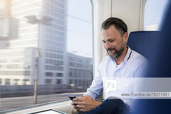 Älterer Mann sitzt in einem Zug und benutzt ein Smartphone