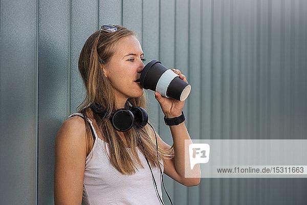 Junge Frau trinkt Kaffee zum Mitnehmen