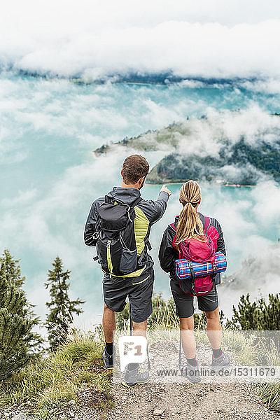 Junges Paar auf einer Wanderung in den Bergen mit Blick auf die Aussicht  Herzogstand  Bayern  Deutschland