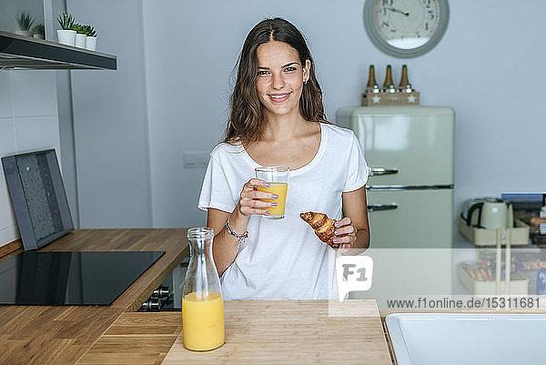 Porträt einer lächelnden jungen Frau beim Frühstück mit Saft und Croissant in der Küche