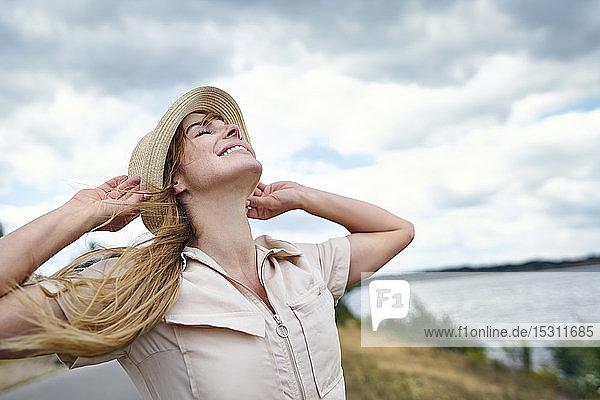 Glückliche Frau mit geschlossenen Augen  die sich am Seeufer zurücklehnt Glückliche Frau mit geschlossenen Augen, die sich am Seeufer zurücklehnt