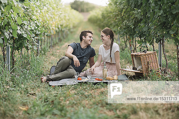 Happy young couple having picnic in the vineyards