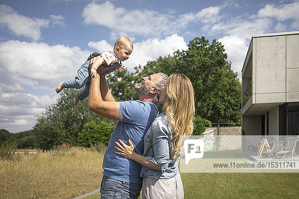 Happy father with mother lifting up baby girl in garden